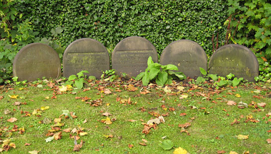 Line of five plain headstones with curved tops