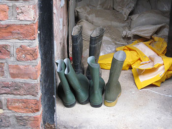 Open door shows wellies, waterproof coat and sandbags in background