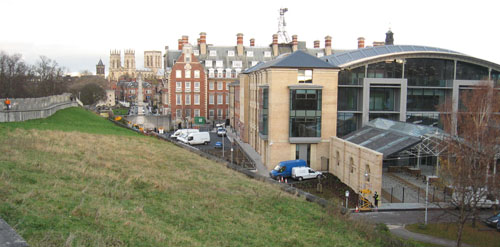 Large new building in foreground, early 20th century red brick building and others, in perspective, Minster on horizon