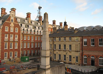 Two buildings, one red brick Edwardian period, one yellow brick (Victorian), stone obelisk of war memorial between, in foreground