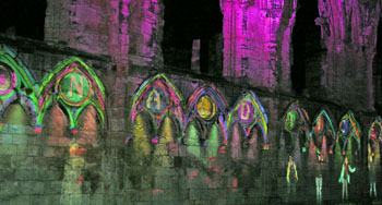 Illuminated abbey and dancing figures