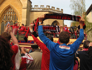Bus surrounded by fans, by St Helen's Church