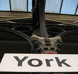 Looking upwards, to station sign: YORK - and ornate top of iron column, and glass and iron roof