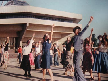 Group of dancers with raised arms, in sunshine, by modern university building