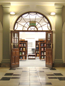 From tiled hallway, looking through open double doors into brightly lit library