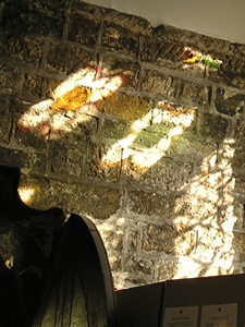 Patterns on church wall through stained glass