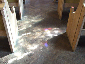 Patterns of light through stained glass on floor of church