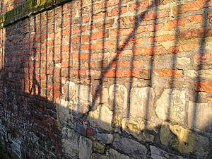 Sunlight through railings, on red brick and stone